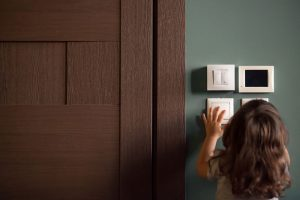 little child girl playing turning light switches