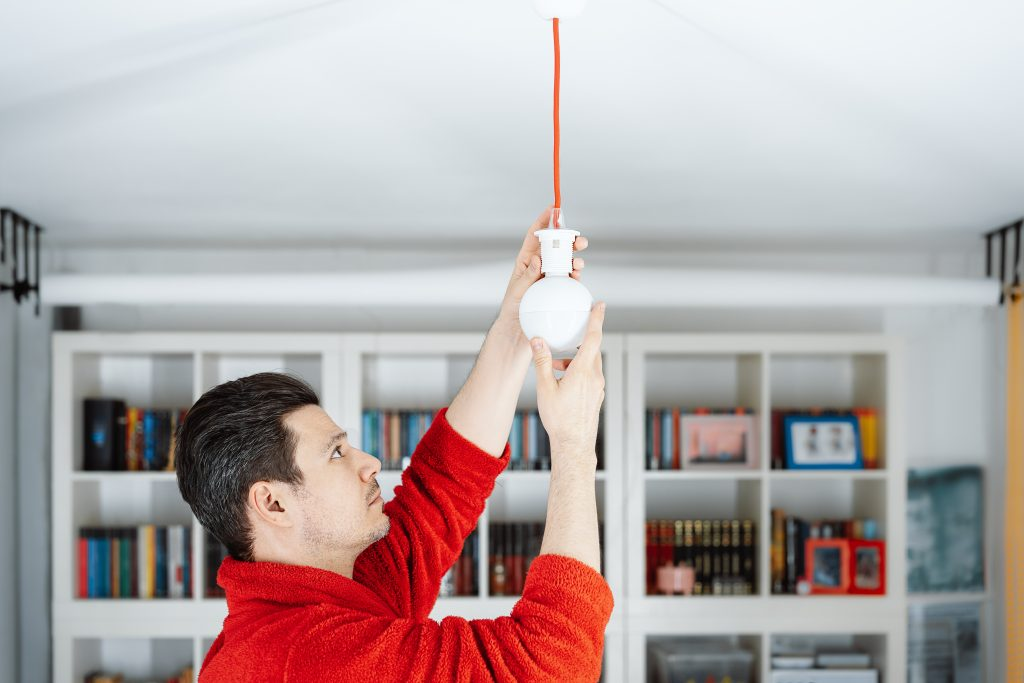 Perth residential electrician fixing a light bulb